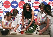 U.S. first lady Michelle Obama cooks with some American kids at James Beard American Restaurant in Milan,Italy, as part of her European trip June 17, 2015.  REUTERS/Stefano Rellandini