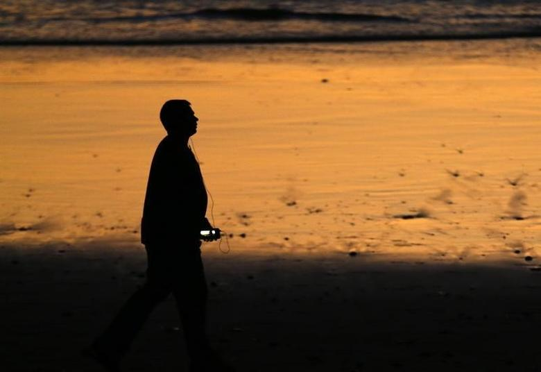 A man listens to music as he walks along the beach past sunset in Encinitas, California October 28, 2014.    REUTERS/Mike Blake