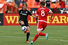 Jun 21, 2015; Washington, DC, USA; D.C. United forward Chris Rolfe (18) shoots the ball as New England Revolution defender Chris Tierney (8) chases in the first half at Robert F. Kennedy Memorial Stadium. D.C. United won 2-1. Mandatory Credit: Geoff Burke-USA TODAY Sports