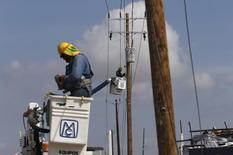 Unos trabajadores reparando postes eléctricos en Baja California, México, sep 18 2014. La estatal mexicana Comisión Federal de Electricidad (CFE) dijo el lunes que lanzará este año la licitación de 24 proyectos de infraestructura de energía eléctrica y gasoductos, que requieren inversiones por unos 150,000 millones de pesos (unos 9,790 millones de dólares).. REUTERS/Henry Romero