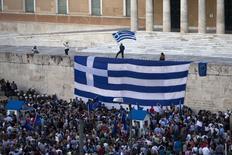 Manifestante exibe bandeira grega na entrada do Parlamento durante protesto pela manutenção da Grécia na zona do euro, em Atenas, nesta segunda-feira. 22/06/2015 REUTERS/Marko Djurica
