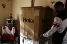 Un hombre desempaca un producto de la firma china Haier en una casa en Caracas, mayo 27 2015. Hace cinco años que se comenzó a construir en Venezuela la fábrica de electrodomésticos de la empresa china Haier, pero aún no produjo ni un solo artefacto que llegara a las tiendas.   REUTERS/Carlos Garcia Rawlins