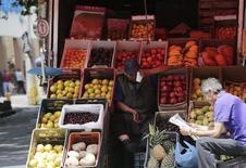 Un vendedor de fruta, esperando clientes junto a un hombre que lee el diario, en una calle en Ciudad de México, 13 de agosto de 2014. La inflación interanual de México se mantuvo en niveles históricamente bajos en la primera quincena de junio, en un 2.87 por ciento, de acuerdo con cifras oficiales divulgadas el miércoles, dentro de la meta del banco central y de acuerdo a lo esperado por analistas. REUTERS/Henry Romero