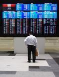 Un hombre mira una pantalla que muestra los índices de mercado en la Bolsa de Tokio, 11 de junio de 2015. Las bolsas de Asia caían el viernes luego de que Grecia no logró llegar a un acuerdo con sus acreedores, mientras que el euro y el dólar operaban en rangos estrechos en momentos en que la saga de la deuda de Atenas mantenía a los inversores cautelosos. REUTERS/Thomas Peter