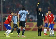 Árbitro Sandro Ricci mostra segundo cartão amarelo ao uruguaio Edinson Cavani, enquanto o chileno Gonzalo Jara observa, durante jogo da Copa América, em Santiago, no Chile. 24/06/2015 REUTERS/Ivan Alvarado