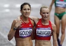 Kara Goucher of the U.S. (L) helps her compatriot Shalane Flanagan after finishing the women's marathon final at the London 2012 Olympic Games at The Mall August 5, 2012.  REUTERS/Mark Blinch