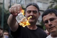 Протестующие жгут купюры валюты евро у здания ЕС в Афинах 28 июня 2015 года. Греция закрыла банки и ввела контроль за капиталом в воскресенье, чтобы ограничить нагрузку на финансовую систему, что выводит на первый план перспективу ее выхода из еврозоны. REUTERS/Alkis Konstantinidis