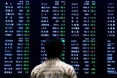 Una mujer parada frente a un tablero electrónico que muestra los índices de mercado en la Bolsa de Tokio, en Tokio, 29 de junio de 2015. Las bolsas de Asia anotaban leves ganancias el miércoles luego de que los inversores aceptaron con resignación la noticia de que Grecia se convirtió en la primera economía desarrollada que incumple el pago de un préstamo al Fondo Monetario Internacional. REUTERS/Thomas Peter