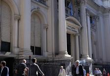 Personas caminando junto al Banco Central de Argentina, en el distrito financiero de Buenos Aires, 20 de agosto de 2014. Argentina registró en abril un déficit presupuestario primario de 17.949 millones de pesos (unos 1.974 millones de dólares), frente a un superávit 671,1 millones de pesos en el mismo mes del 2014, informó el miércoles el Gobierno. REUTERS/Marcos Brindicci