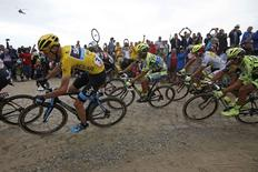 Team Sky rider Chris Froome of Britain (L), race leader and yellow jersey holder, and Tinkoff-Saxo rider Alberto Contador of Spain (C) cycle on a cobble-stoned section during the 223.5-km (138.9 miles) 4th stage of the 102nd Tour de France cycling race from Seraing in Belgium to Cambrai, France, July 7, 2015. REUTERS/Eric Gaillard