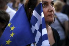 A pro-Euro protester holds a European Union and a Greek national flag during a rally in front of the parliament building in Athens, Greece, July 9, 2015.  REUTERS/Alkis Konstantinidis