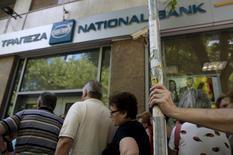Les banques grecques devront être recapitalisées de 10 à 14 milliards d'euros et auront besoin d'un délai supplémentaire avant leur réouverture même en cas d'accord dimanche entre le gouvernement et ses partenaires européens sur une nouvelle aide financière au pays, a déclaré à Reuters un dirigeant du secteur bancaire grec. /Photo prise le 9 juillet 2015/REUTERS/Yannis Behrakis
