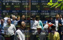 People are reflected in a board displaying stock indices in Tokyo July 10, 2015.  REUTERS/Thomas Peter