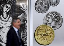 Un hombre pasa junto a una serie de monedas antiguas en el centro de Atenas, 13 de julio de 2015. Los líderes de la zona euro fijaron el lunes las condiciones para negociar el tercer paquete de rescate a Grecia, a fin de mantener el endeudado país dentro del bloque monetario. REUTERS/Jean-Paul Pelissier