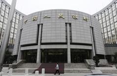Una persona camina frente a la sede del Banco Popular Chino, en Beijing, 25 de junio de 2013. China flexibilizó las reglas para ciertos inversores extranjeros a largo plazo en su mercado interbancario retirando los límites a la cantidad de inversiones, una medida que podría fortalecer el naciente mercado financiero del gigante asiático. REUTERS/Jason Lee