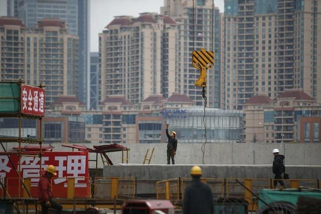 Labourers work at a construction site for a new building in Shanghai, March 5, 2015. REUTERS/Aly Song