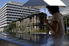 Женщина проходит мимо здания Банка Японии в Токио 15 июля 2015 года. Банк Японии в среду сократил прогноз экономического роста, но воздержался от введения новых стимулов, полагая, что ожидаемый подъем потребления подтолкнет инфляцию к его 2-процентному ориентиру. REUTERS/Yuya Shino