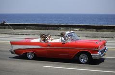 En la imagen de archivo, turistas en un coche estadounidense Chevrolet en el Malecón de La Habana el 21 de mayo de 2013. El grupo de transporte marítimo español Baleària dijo el viernes que ya ha recibido las licencias necesarias para poder operar entre Estados Unidos y Cuba, aunque tiene que esperar la autorización del gobierno cubano antes de iniciar las conexiones. REUTERS/Desmond Boylan