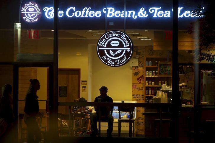 A man sits in a The Coffee Bean & Tea Leaf cafe in the rain in the Manhattan borough New York May 27, 2015. REUTERS/Carlo Allegri