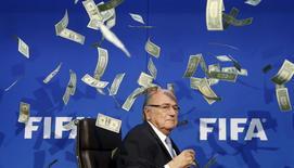 Comediante britânico atira dinheiro falso em Blatter durante entrevista coletiva em Zurique.  20/7/2015.  REUTERS/Arnd Wiegmann