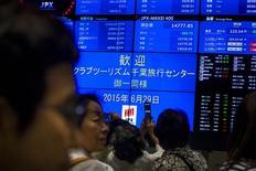 Visitantes miran una pantalla que muestra los índices de mercado, en la Bolsa de Tokio, 29 de junio de 2015. Las bolsas de Asia subían el martes apoyadas por un repunte del Nasdaq en la sesión previa, mientras que los precios del oro se recuperaban tras caer más de un 4 por ciento en la sesión anterior a mínimos de cinco años. REUTERS/Thomas Peter