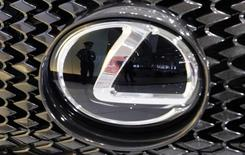 A security guard is reflected in the logo of a Toyota Motor Corp's Lexus car at the company's showroom in Tokyo May 31, 2013. REUTERS/Toru Hanai