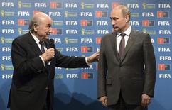 Russia's President Vladimir Putin (R) and FIFA President Sepp Blatter take part in the official hand over ceremony for the 2018 World Cup scheduled to take place in Russia, in Rio de Janeiro July 13, 2014. REUTERS/Alexey Nikolsky/RIA Novosti/Kremlin/Files