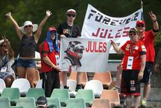 F1 supporters hold a banner in memoriam of former French Formula One driver Jules Bianchi during the first practice session of the Hungarian F1 Grand Prix at the Hungaroring circuit, near Budapest, Hungary July 24, 2015. The popular Bianchi died in hospital last Friday, nine months after his Marussia car slammed into a recovery tractor at the Japanese Grand Prix. REUTERS/Laszlo Balogh