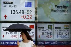 Una mujer camina junto a un tablero electrónico que muestra la tasa cambiaria entre varias divisas, incluyendo el yen japonés contra el euro, afuera de una correduría en Tokio, 13 de julio de 2015. Las bolsas de Asia rebotaban el martes desde los mínimos de la sesión luego de una nueva caída de las acciones chinas, mientras que algunos inversores se refugiaron de la volatilidad del mercado en los activos más seguros como los bonos soberanos y el yen japonés. REUTERS/Issei Kato