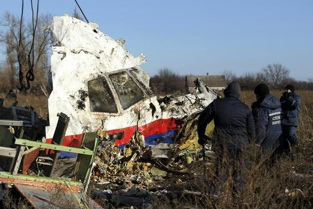 Local workers transport a piece of wreckage from Malaysia Airlines flight MH17 at the site of the plane crash near the village of Hrabove (Grabovo) in Donetsk region, eastern Ukraine November 20, 2014. REUTERS/Antonio Bronic