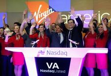 Virgin America Inc. President and Chief Executive Officer David Cush (C) waves after ringing the opening bell of the trading session with NASDAQ President and Chief Executive Officer Robert Greifeld (3rd R) as Virgin America Inc. celebrated its initial public offering at the NASDAQ Market Site in New York, November 14, 2014.  REUTERS/Mike Segar