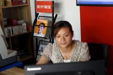 Zheng Liying looks at a computer screen in front of a picture of Alibaba founder Jack Ma, seen on the cover of a publication, at Zheng's Alibaba rural service centre in Jinjia Village, Tonglu, Zhejiang province, China, July 20, 2015. REUTERS/Aly Song