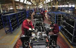 Trabajadores instalan el chasís de un camión en la línea de producción de la fábrica de camiones de Anhui Jianghuai Automobile Co. (JAC Motors) en Hefei, 5 de mayo de 2014. Los precios de las materias primas caían nuevamente el lunes y algunas se desplomaban a mínimos de varios años por el temor a una sobreoferta debido a la débil demanda en China, que el lunes informó que su actividad fabril cayó más de lo esperado el mes pasado. REUTERS/Stringer