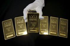 Сотрудник Korea Gold Exchange демонстрирует слитки золота. Сеул, 31 июля 2015 года. Цены на золото близки к минимуму 5,5 лет на фоне роста курса доллара, вызванного комментарием чиновника ФРС в пользу повышения процентных ставок в сентябре. REUTERS/Kim Hong-Ji