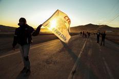 """Una mujer sostiene una bandera que dice """"Cobre para Chile"""", durante una protesta en el lugar donde murió un trabajador de Codelco, en la minera de cobre El Salvador, en El Salvador, Chile. 24 de julio de 2015. Los trabajadores de empresas contratistas de la estatal chilena Codelco afirmaron el viernes que confían en lograr un acuerdo a través del diálogo iniciado en la víspera, que ponga fin a la movilización de más de dos semanas en el mayor productor mundial de cobre. REUTERS/Francisco Fuentes"""