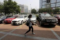A woman walks past Mercedes Benz cars displayed for sale outside a store in Beijing, China August 11, 2015. REUTERS/Jason Lee