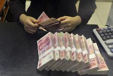 La Chine a dévalué le yuan mardi après une série d'indicateurs macroéconomiques décevants, ramenant la monnaie vers son plus bas niveau en près de trois ans. Le point médian de la bande de fluctuation quotidienne autorisée du yuan est fixé à 6,2298 pour un dollar, contre 6,1162 lundi, soit une dépréciation de près de 2%. /Photo prise le 20 avril 2015/REUTERS