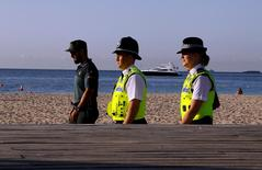 British police officers Anderson (R) and Williams (C) patrol with a Spanish civil guard officer in the seaside of Magaluf, on the Spain's Balearic Islands of Mallorca, August 11, 2015. REUTERS/Enrique Calvo