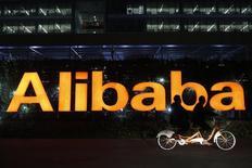 Personas andan en una bicicleta doble junto al logo de Alibaba Group, en la sede de la compañía a las afueras de Hangzhou, 10 de noviembre de 2014. Alibaba Group Holding Ltd reportó el miércoles un alza del 28 por ciento en sus ingresos durante el trimestre finalizado en junio, pero la cifra es menor a las estimaciones de analistas y muestra una desaceleración del crecimiento a su ritmo más bajo en más de tres años. REUTERS/Aly Song/Files