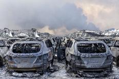 Поврежденные взрывом автомобили. Тяньцзинь, 13 августа 2015 года. Два мощных взрыва в китайском портовом Тяньцзине, где сосредоточены склады с ядовитыми химикатами и газом, унесли не менее 44 жизней, помешали импорту железной руды и прибытию нефтяных танкеров. REUTERS/Stringer
