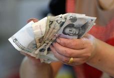 """La decisión adoptada esta semana por China de debilitar el yuan podría evitar más """"ajustes"""" similares, por lo que la divisa se movería en ambas direcciones mientras se estabiliza la economía, afirmó el domingo Ma Jun, economista jefe del banco central.  En la imagen, un vendedor sostiene yuanes en un mercado en Pekín. 12 agosto 2015. REUTERS/Jason Lee"""