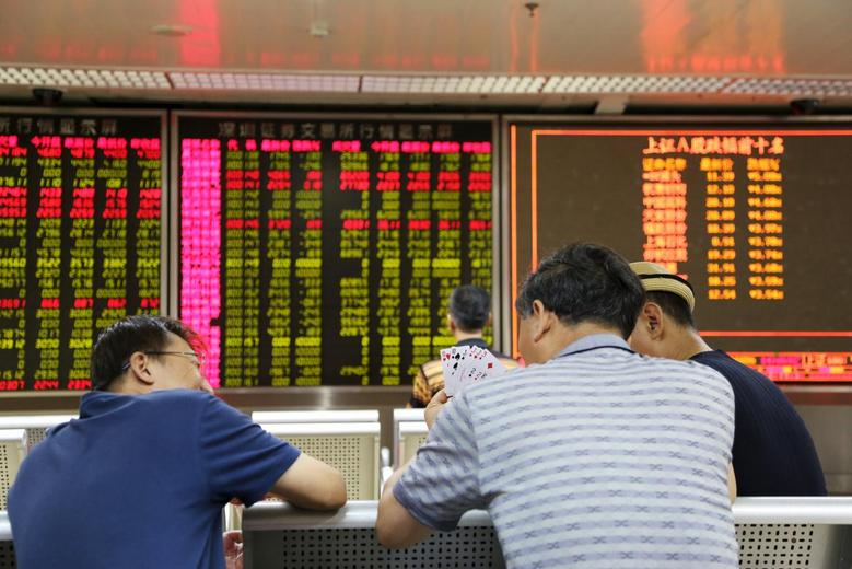 Investors play cards in front of an electronic board showing stock information at a brokerage house in Beijing, August 17, 2015. REUTERS/Stringer