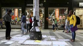 Personas miran anuncios de trabajos pegados en un poste en el centro de Sao Paulo, 19 de marzo de 2015.  La tasa de desempleo de Brasil no ajustada por estacionalidad subió a 7,5 por ciento en julio, el nivel más alto en más de cinco años, dijo el jueves el estatal Instituto Brasileño de Geografía y Estadística (IBGE). REUTERS/Paulo Whitaker