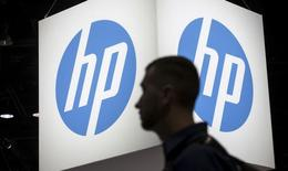 An attendee at the Microsoft Ignite technology conference walks past the Hewlett-Packard (HP) logo in Chicago, Illinois, May 4, 2015. REUTERS/Jim Young