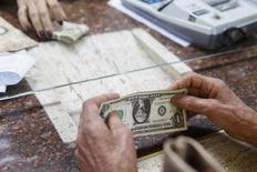 Mulher troca dólar norte-americano por bolívares em casa de câmbio de Caracas, na Venezuela. 24/02/2015 REUTERS/Carlos Garcia Rawlins