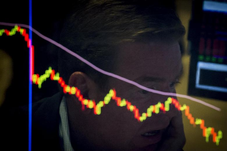 A specialist trader is reflected in a screen at his post on the floor of the New York Stock Exchange, August 21, 2015. REUTERS/Brendan McDermid
