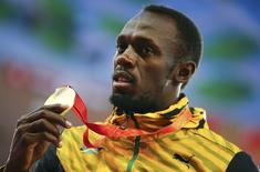Usain Bolt of Jamaica presents his gold medal after winning the men's 100m event during the 15th IAAF World Championships at the National Stadium in Beijing, China August 24, 2015.  REUTERS/Damir Sagolj