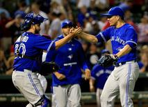 Aug 25, 2015; Arlington, TX, USA; Toronto Blue Jays relief pitcher Roberto Osuna (right) celebrates with catcher Dioner Navarro (30) after recording the final out against the Texas Rangers at Globe Life Park in Arlington. Kevin Jairaj-USA TODAY Sports