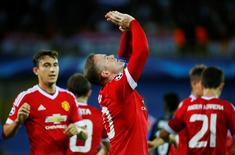 Wayne Rooney celebrates after scoring the first goal for Manchester United.  Reuters / Yves Herman