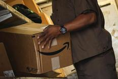 A UPS worker carries an Amazon box to be delivered in New York July 24, 2015. REUTERS/Eduardo Munoz